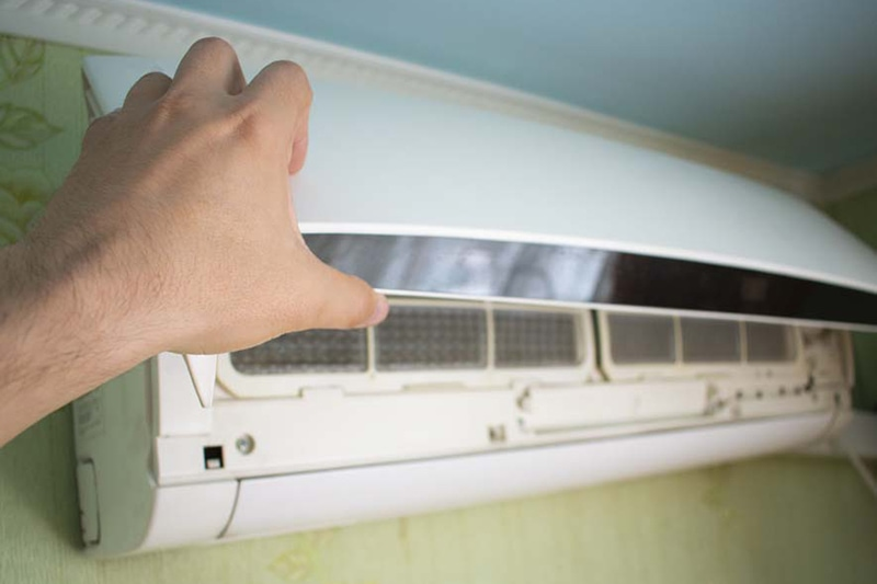 Hand opening the lid of the air conditioner, Is It Normal for My AC to Turn On & Off? | HVAC Repair | Bremerton, WA