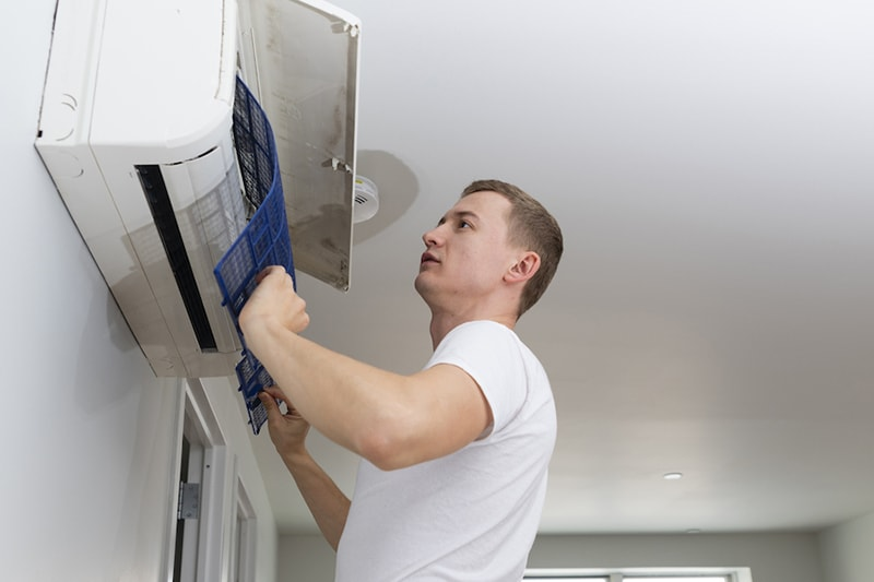 Young man cleaning filters in the air-conditioning split device, The Problem With Clogged Air Filters | Indoor Air Quality, HVAC Service