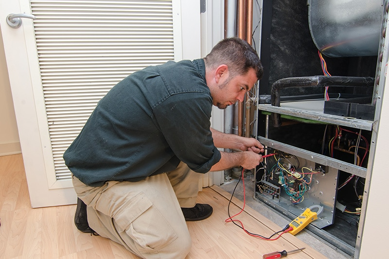 HVAC technician working on a residential heat pump, HVAC Maintenance Checklist for Homeowners | Port Orchard, WA | Dana's